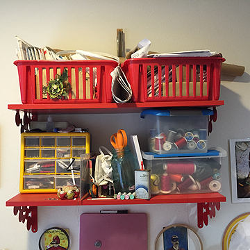 The baskets on the top shelf are full of patterns and the bottom shelf holds her tools, notions, and threads.